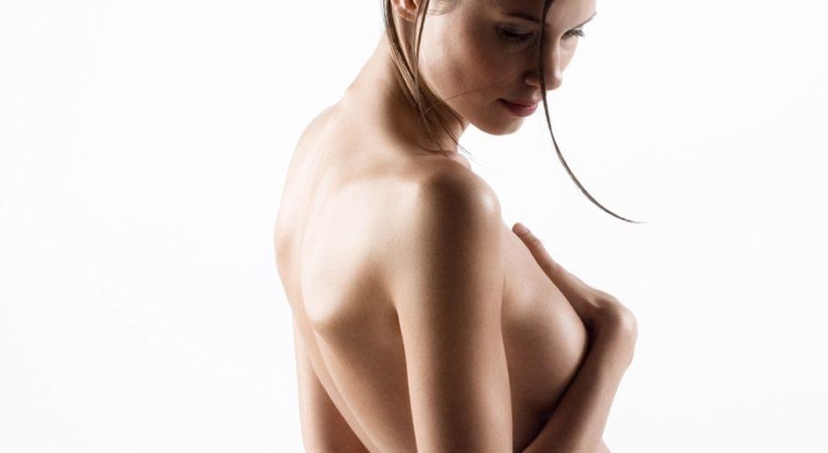 обнаженная девушка прикрывает грудь