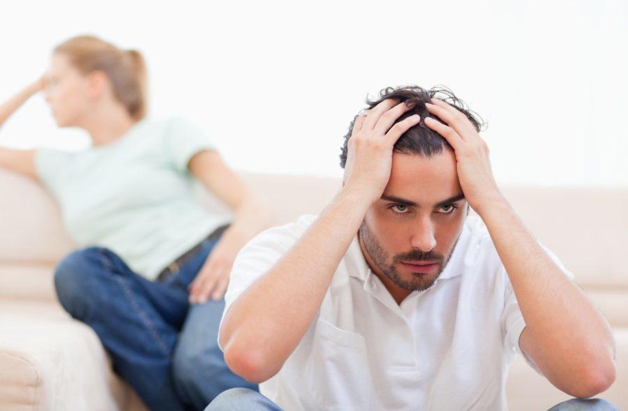 мужчина держится за голову женщина сидит на диване