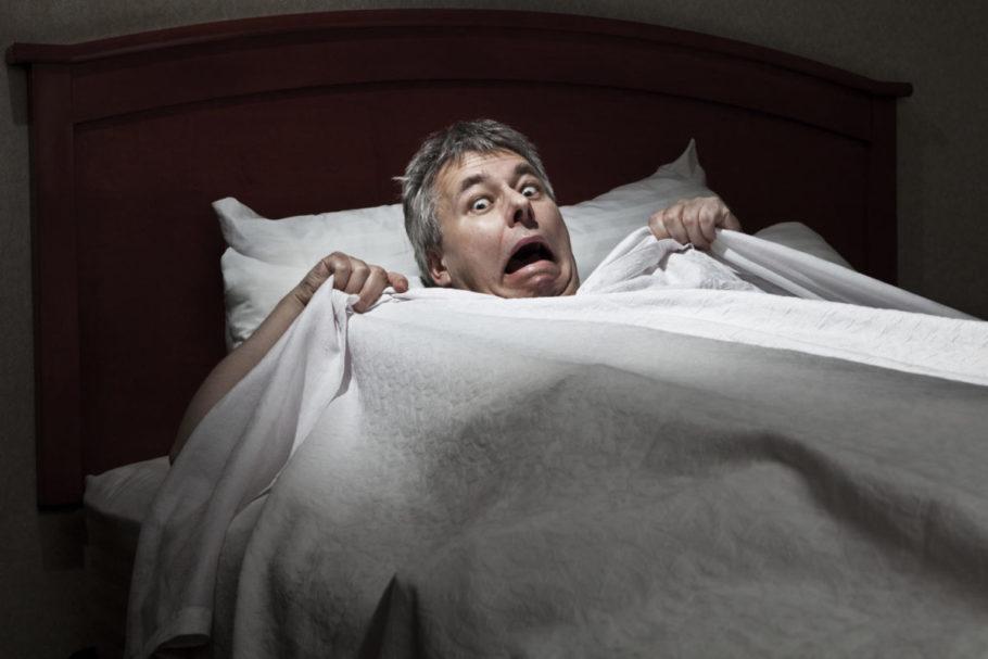 испуганный мужчина держит одеяло