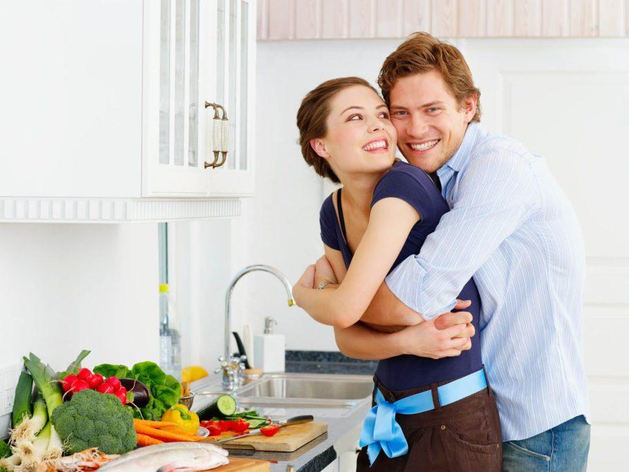 парень обнимает девушку на кухне