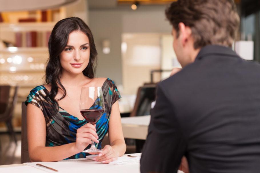 девушка с бокалом вина сидит напротив мужчины