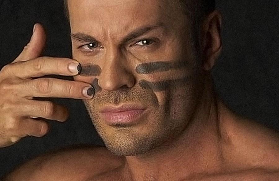 Мужчина наносит камуфляжную раскраску на лицо