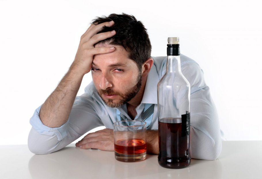 сонный мужчина перед бутылкой алкоголя