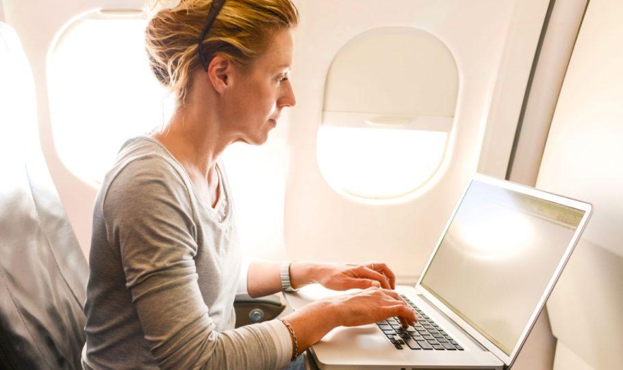 Девушка работает за ноутбуком в самолете