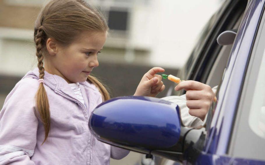 Девочка берет конфету через открытое окно в машине