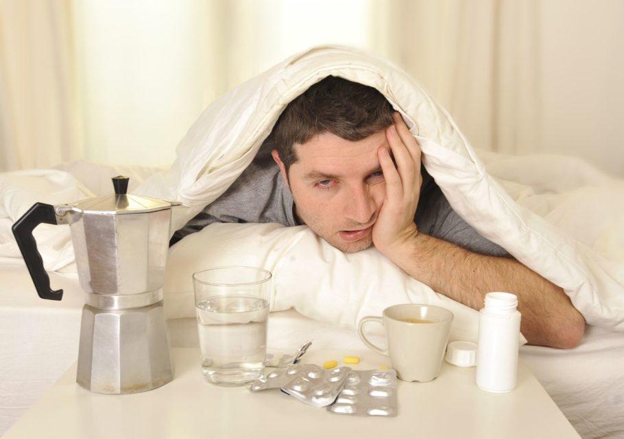 мужчина рядом со столом с таблетками и водой