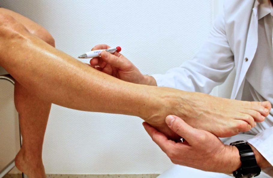 врач держит в руках ногу пациента