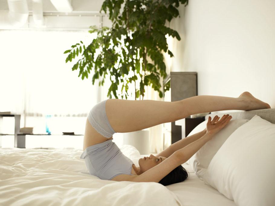 девушка выполняет упражнение на кровати