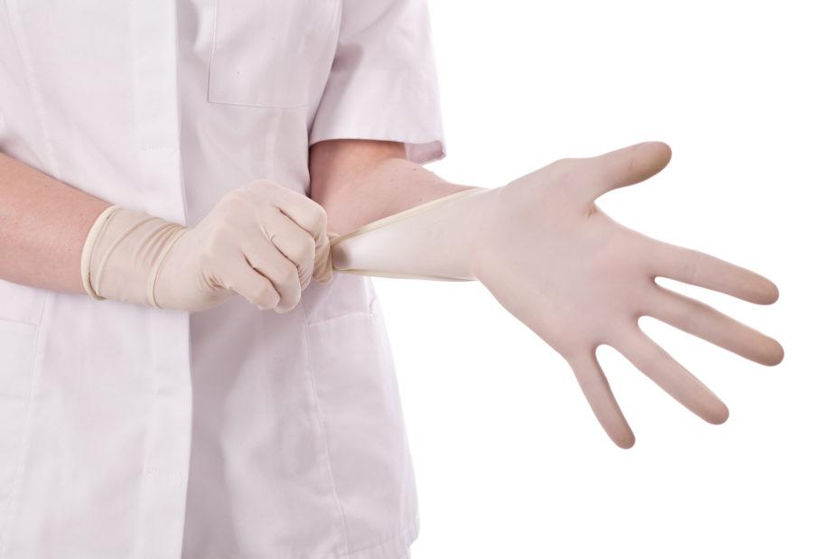 врач надевает перчатки