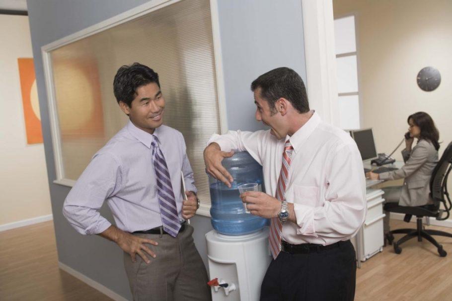 Двое мужчин разговаривают возле кулера с водой