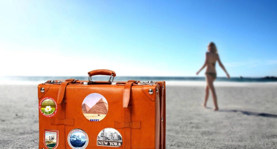 Чемодан и девушка на пляже