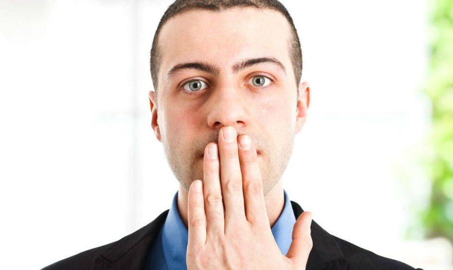 мужчина закрывает рот рукой