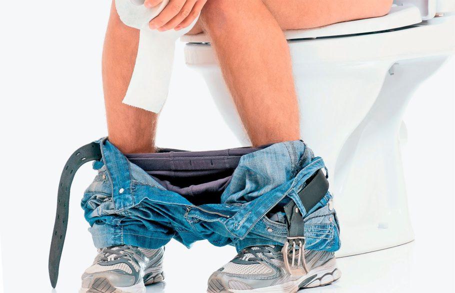 мужчина сидит на унитазе и держит туалетную бумагу в руках