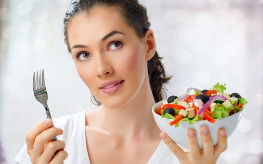 Девушка с тарелкой салата в руках размышляет