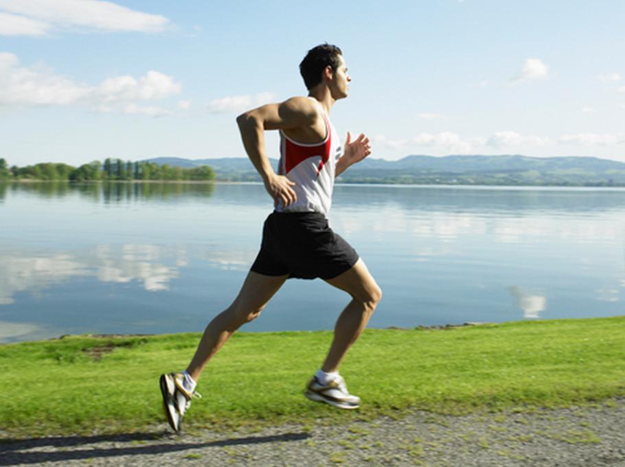 Мужчина занимается бегом на берегу водоема