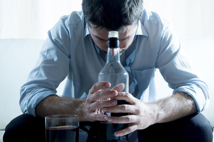 мужчина склонился над бутылкой алкоголя