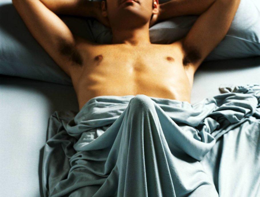 возбужденный мужчина лежит в кровати