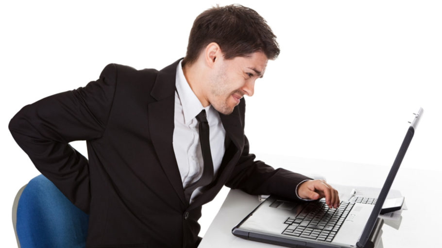мужчина держится за спину сидя перед ноутбуком