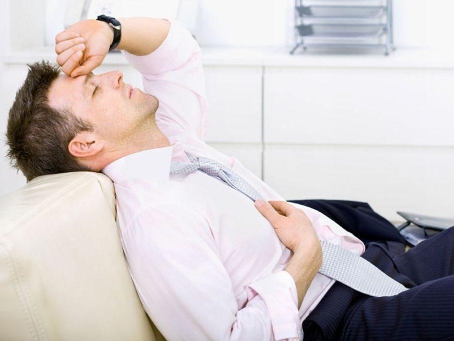 Мужчина полулежит на диване положив руку на лоб