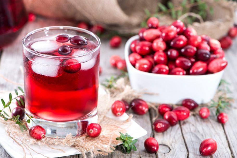 Отвар клюквы в стакане и ягоды клюквы в тарелке