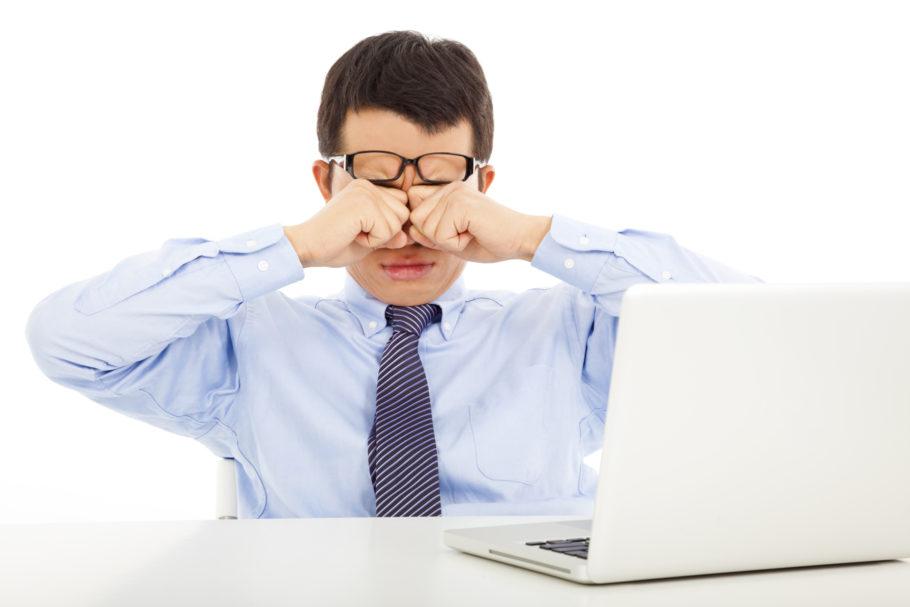 Молодой человек устал за компютером и трет глаза