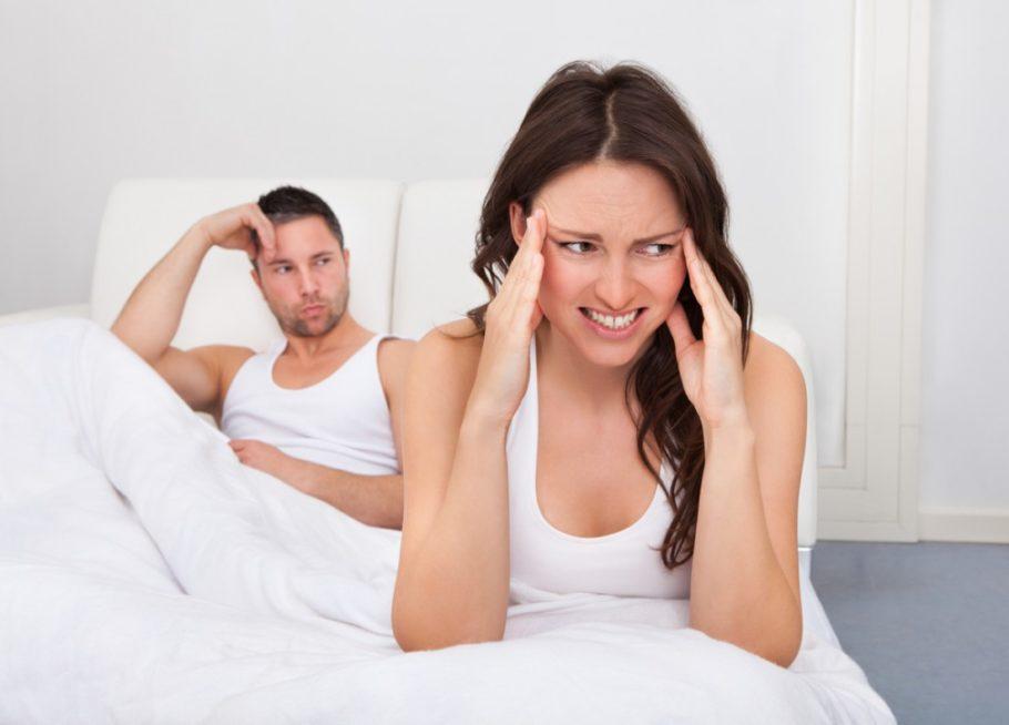 женщина держится за голову сидя на кровати
