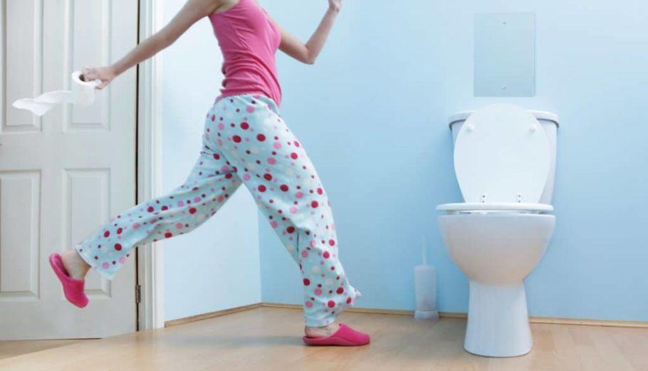Девушка бежит к унитазу с рулоном туалетной бумаги