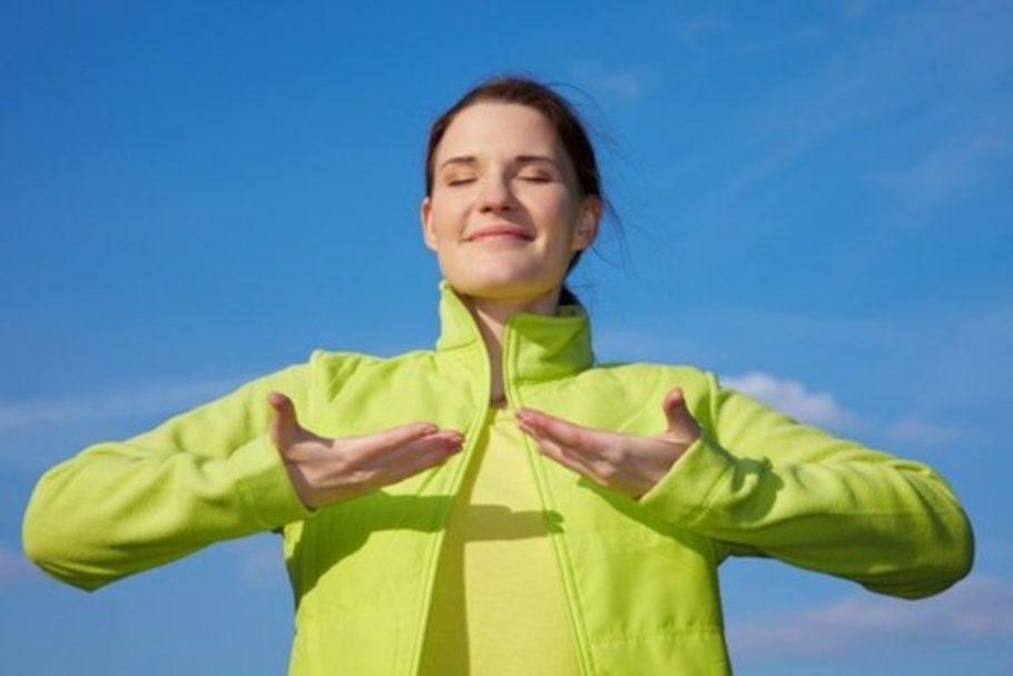Девушка проводит дыхательные упражнения на природе