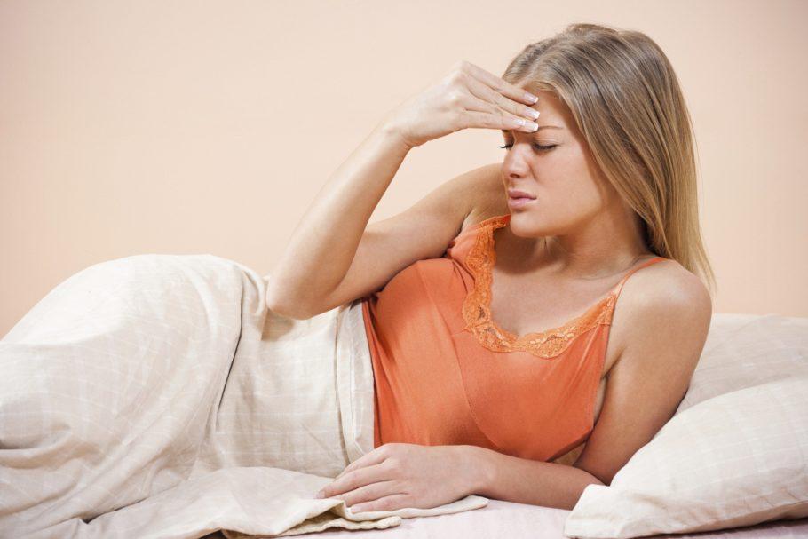 Девушка лежа держится за голову, болит голова