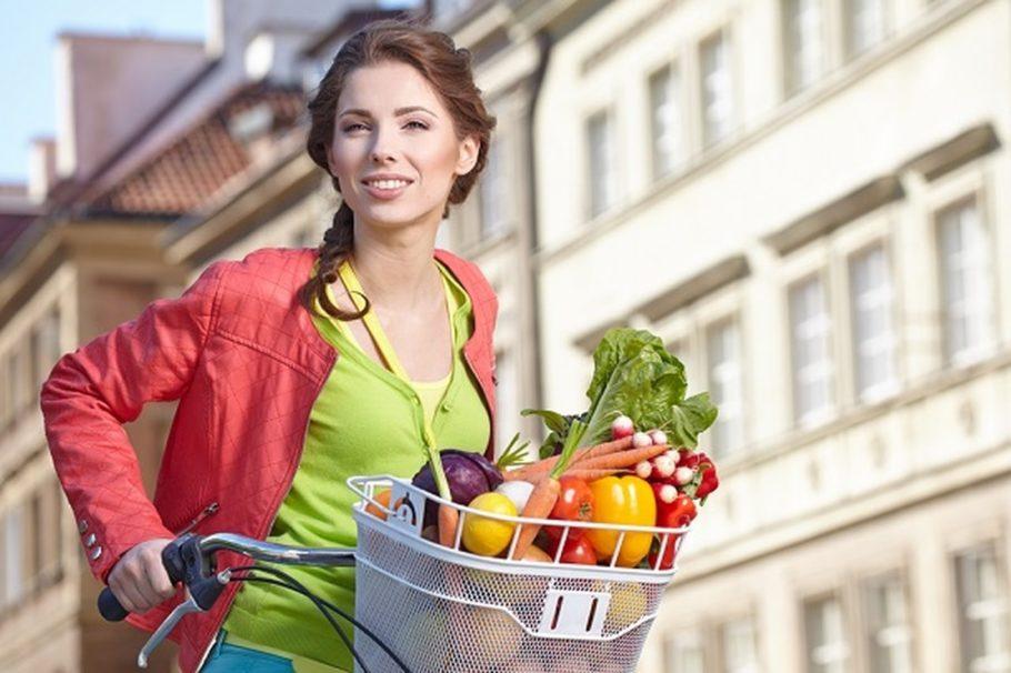 девушка на велосипеде с корзиной продуктов