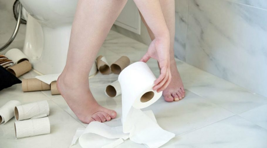 Девушка в туалете держит туалетную бумагу