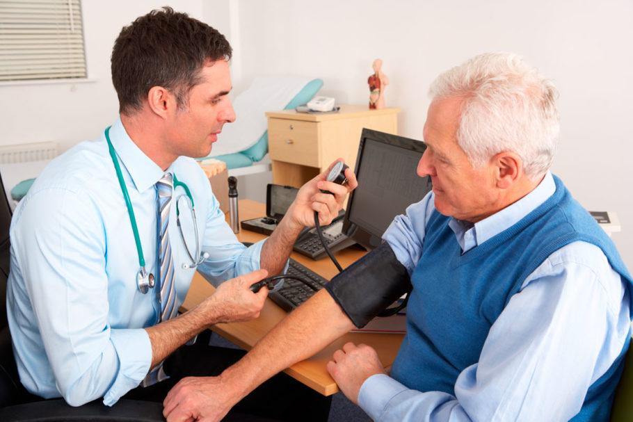 Специалист измеряет артериальное давление пожилому мужчине