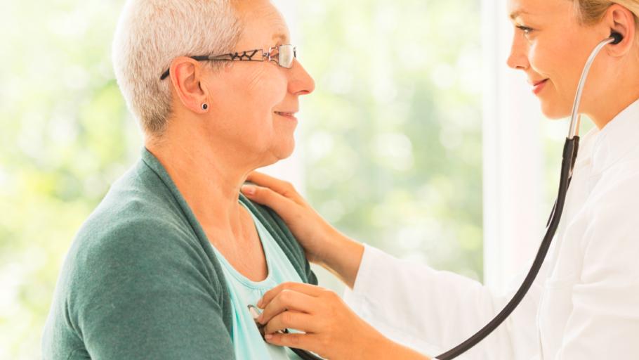 Доктор слушает с помощью стетоскопа пациентку