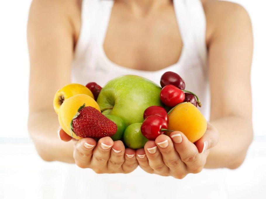 девушка держит в руках фрукты и ягоды