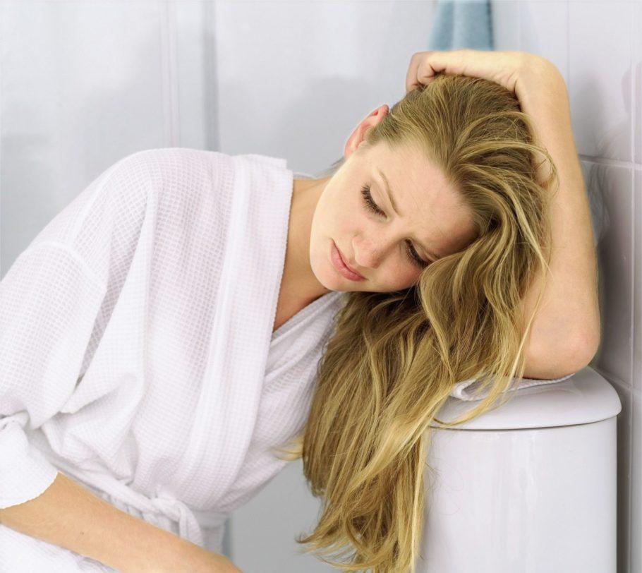 Женщина сидит опершись рукой на сливной бачок