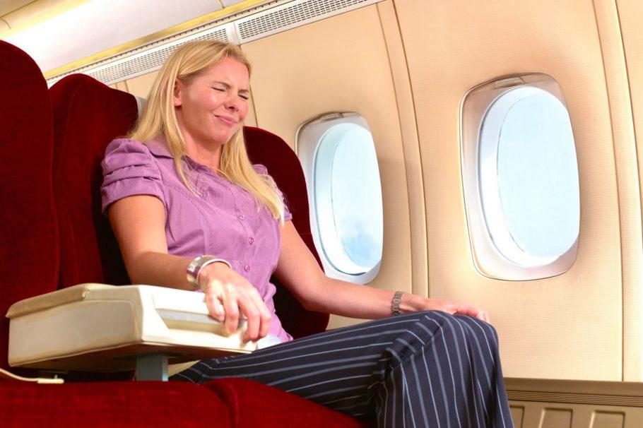 женщина держится за поручни в самолёте