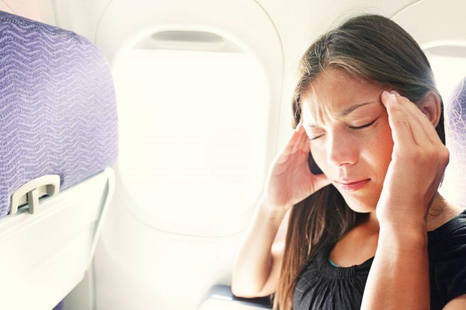 женщина в самолёте держится за голову