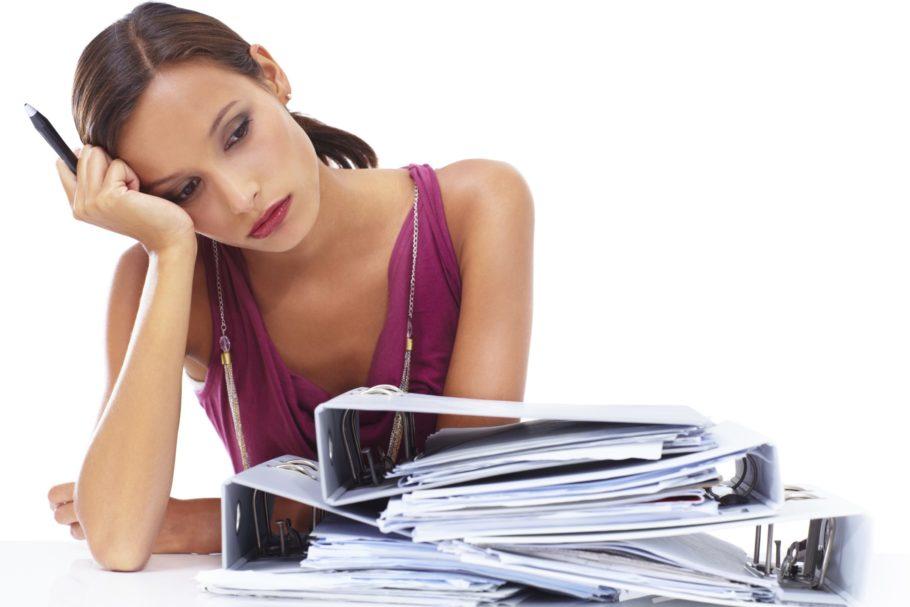 женщина склонилась над столом с папками