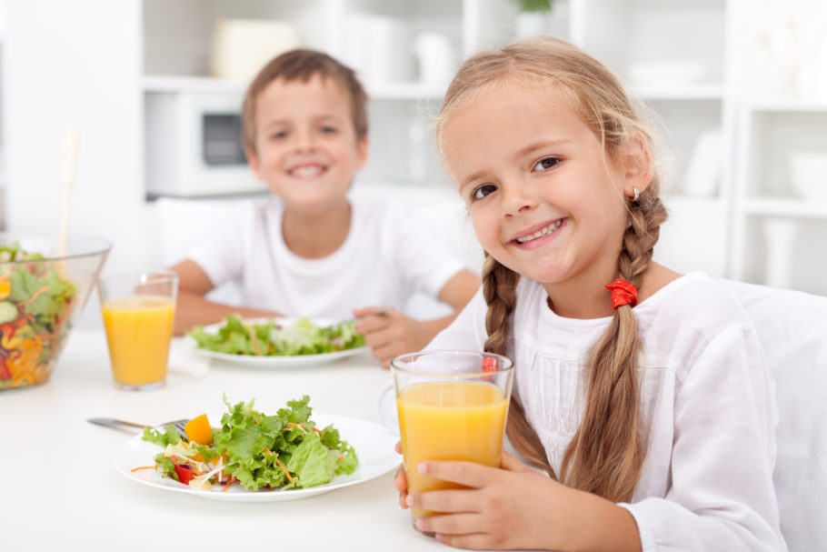 Мальчик и девочка пьют сок и едят салат