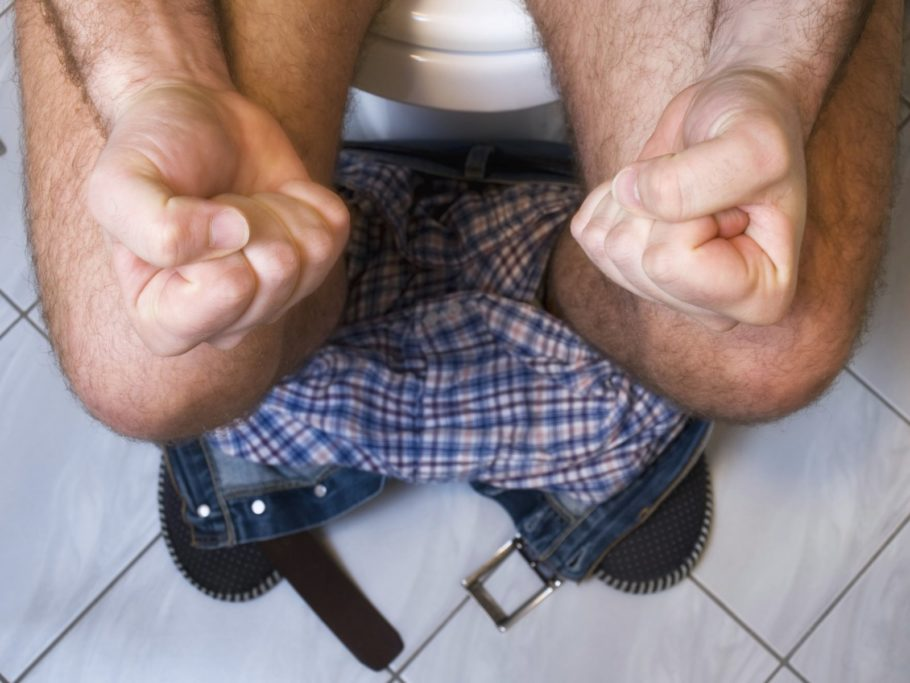 Мужчина сжимает кулаки сидя на унитазе