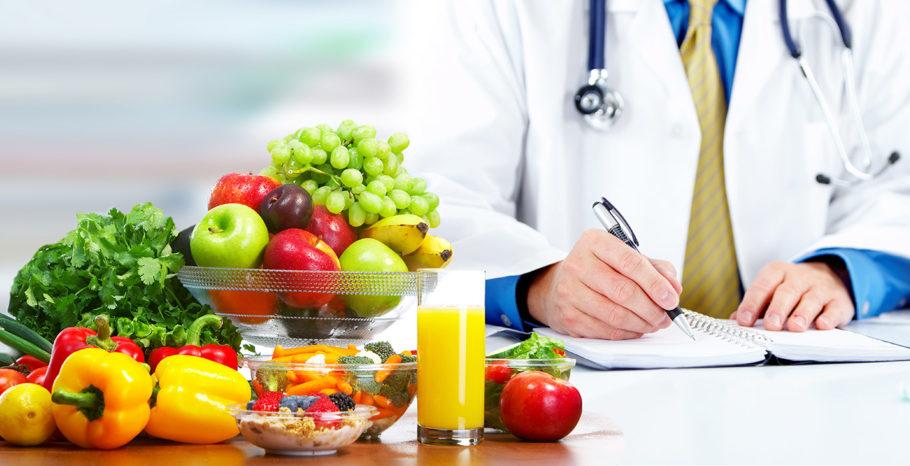 Доктор сидит за столом с фруктами и овощами