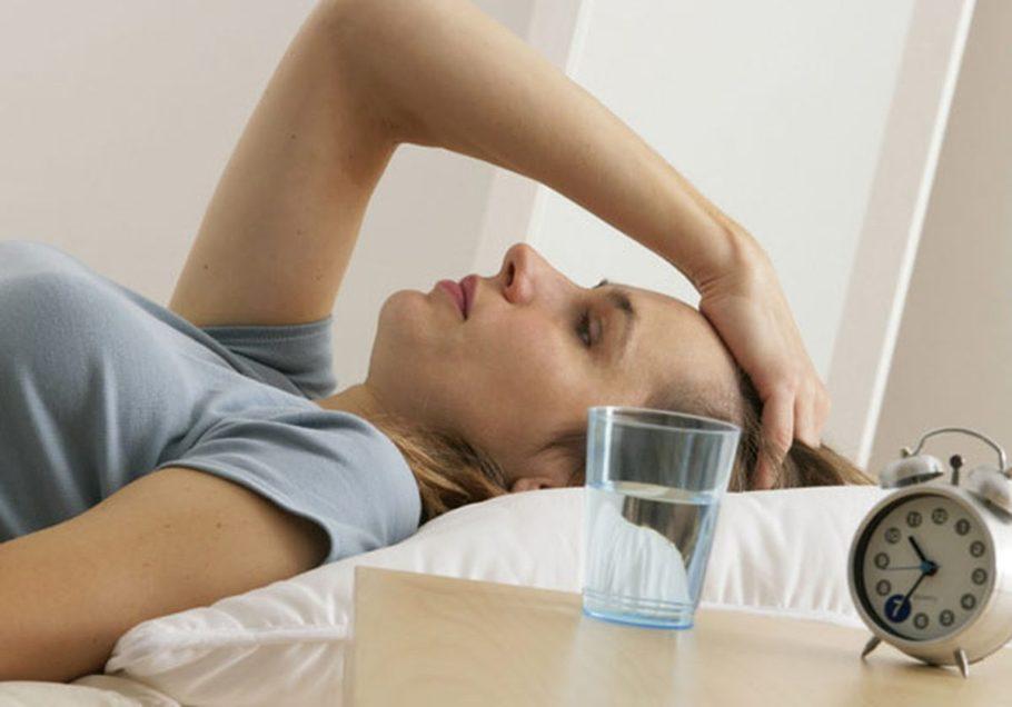 девушка лежит на кровате, на тумбочке стоит стакан