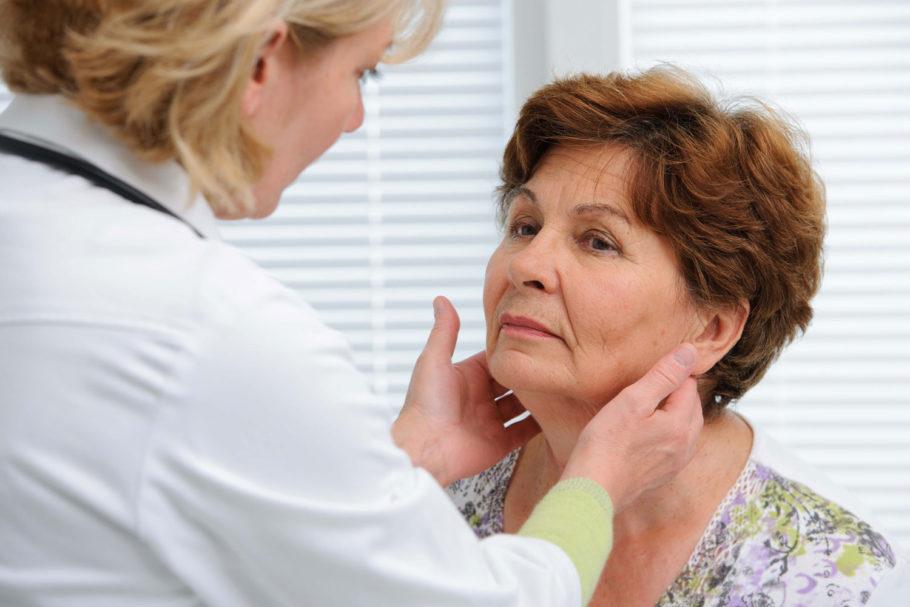 Доктор осматривает шею у женщины