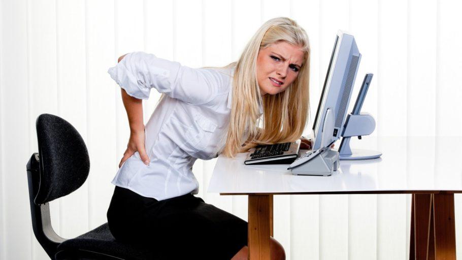 девушка держится за голову перед компьютером