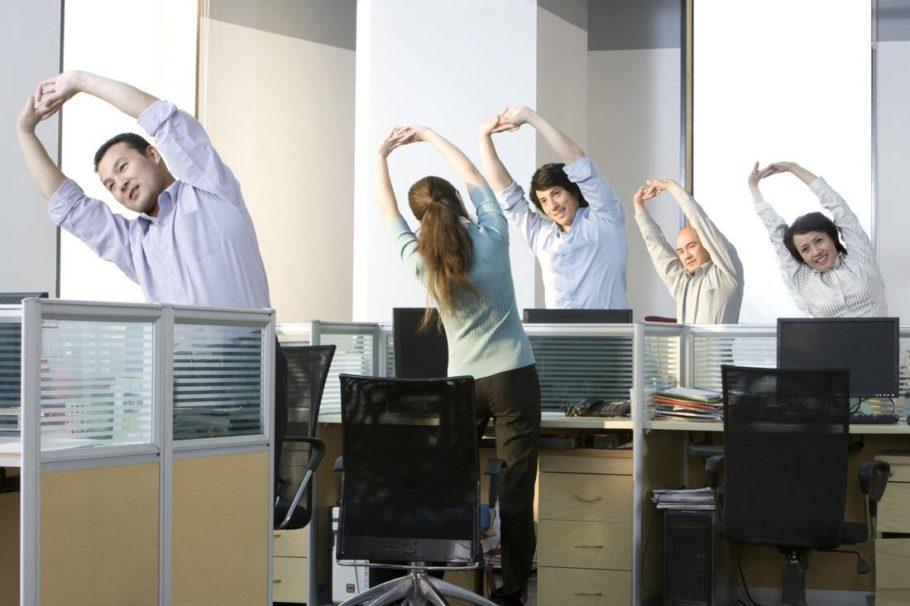 работники в офисе делают зарядку