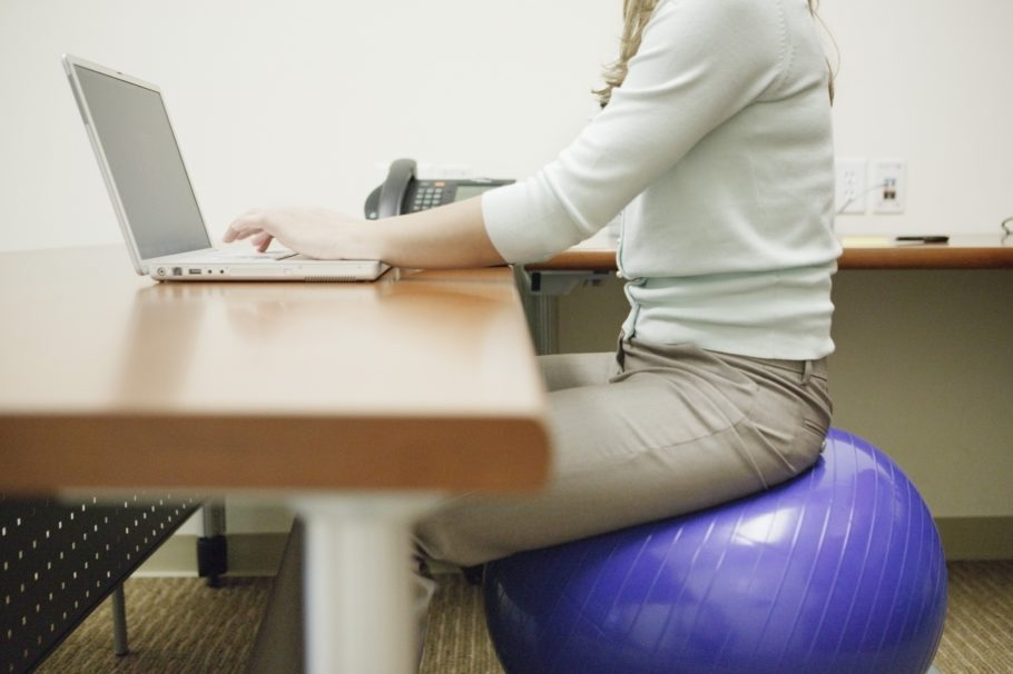 девушка на гимнастическом шаре за компьютером