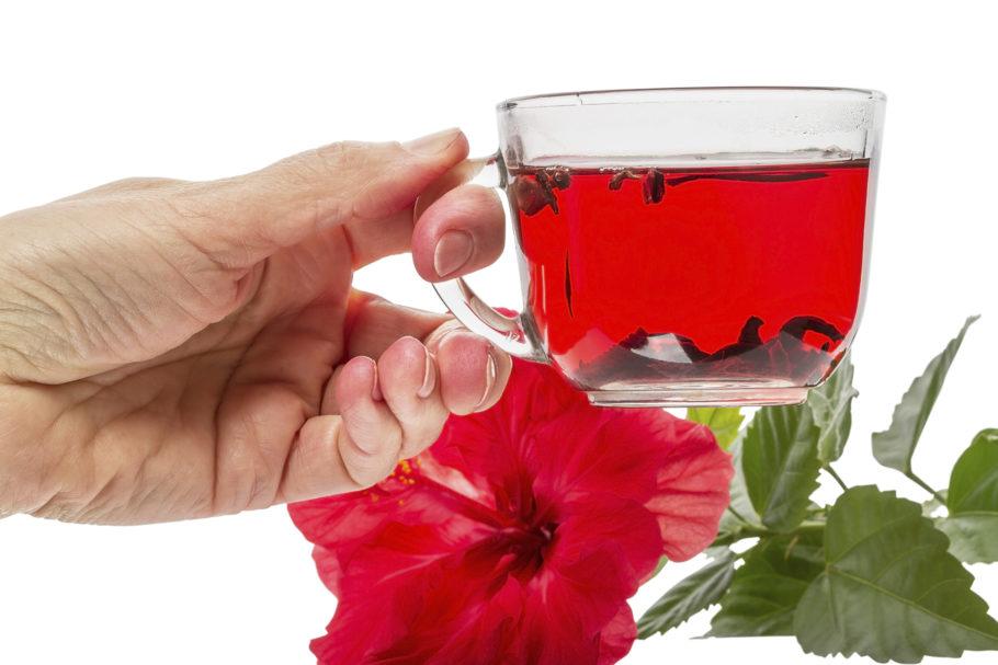 Рука держит чашку с чаем каркаде