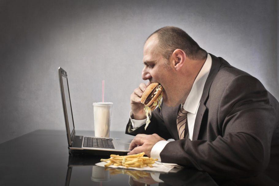 мужчина ест гамбургер перед ноутбуком