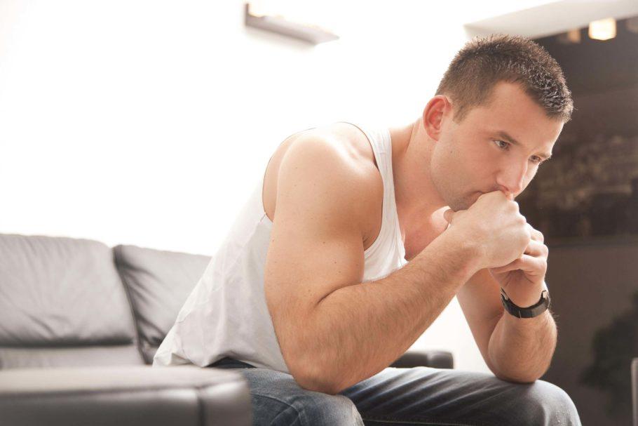 мужчина держится за подбородок сидя на диване