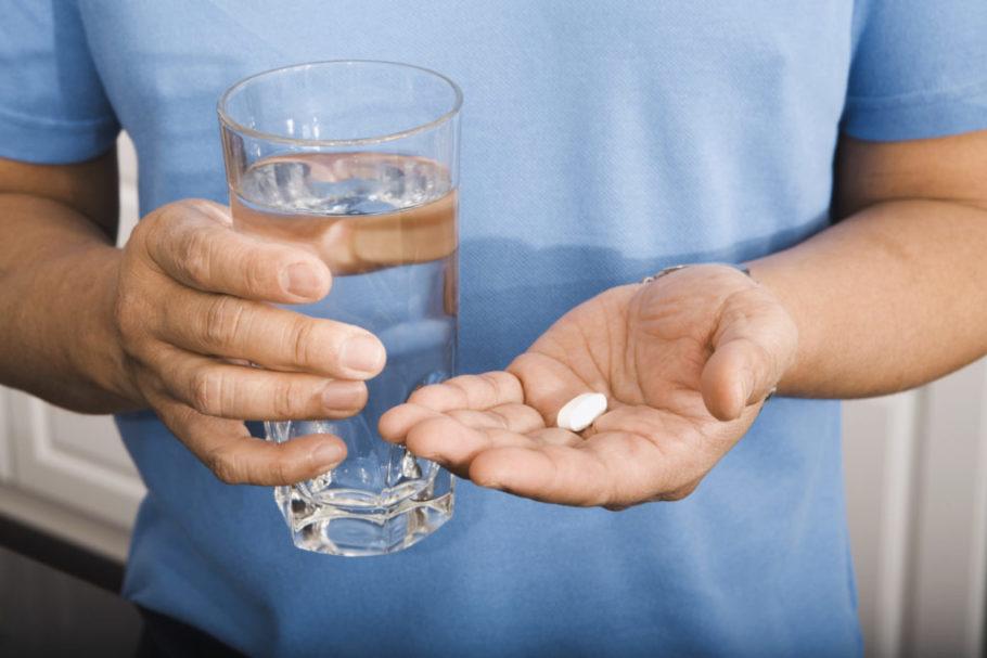 Мужчина держит таблетки и стакан с водой в руках